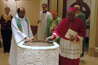 LWF General Secretary Ishmael Noko, left, and Archbishop Wilton Gregory, Archdiocese of Atlanta, right, stop at the font as they processed at the start of the JDDJ celebration.