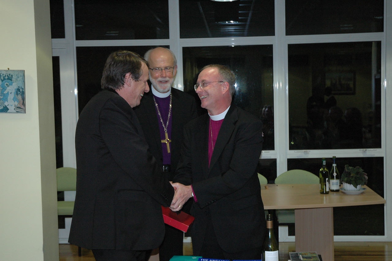 Bishop Michael Burk, right, ELCA Southeastern Iowa Synod, presents a copy of Evangelical Lutheran Worship to the Rev. Canon Kenneth Kearon, general secretary, Anglican Consultative Council.  ELCA Presiding Bishop and LWF President Mark Hanson is in the center background.