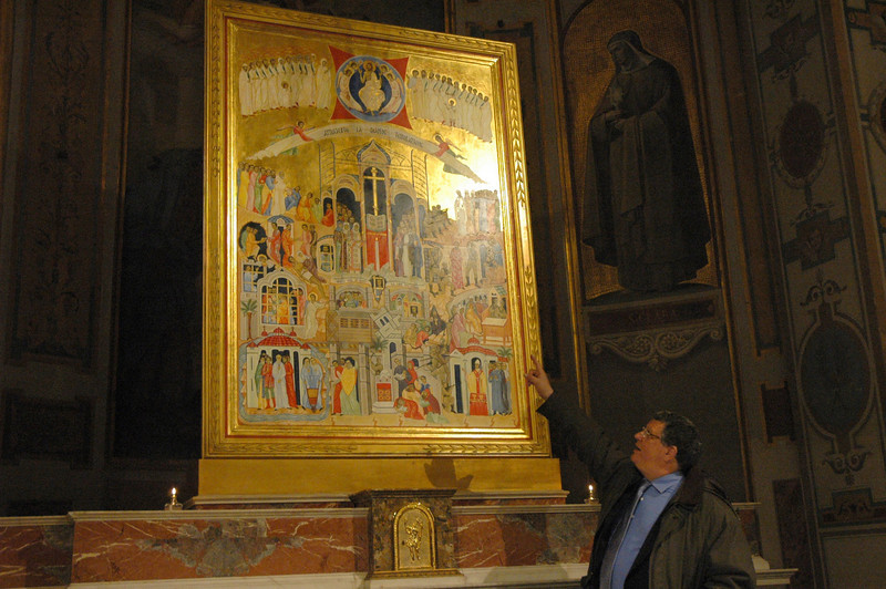 Claudio Mario Betti explains a mosaic that shows modern saints who dedicated their lives serving people in need.  The mosaic is displayed at the Ecumenical Basilica St. Bartholomew on Tiber Island, Rome.