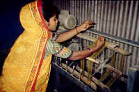 A woman reels silk at a small RDRS factory.