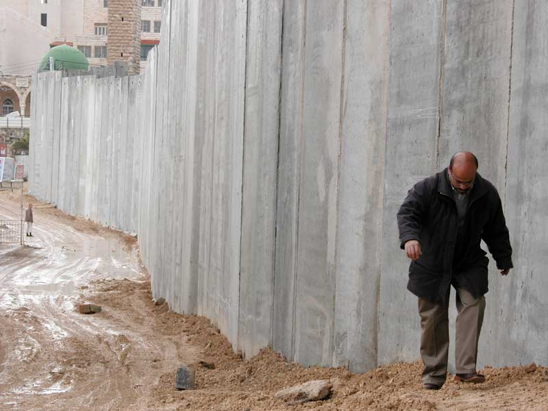 """The ELCA delegation visited the Israeli """"separation"""" or """"security"""" wall. This section runs through the village of Abu Dis near Jerusalem. The ELCA bishops in the delegation say the wall will only heighten tensions between Israelis and Palestinians."""
