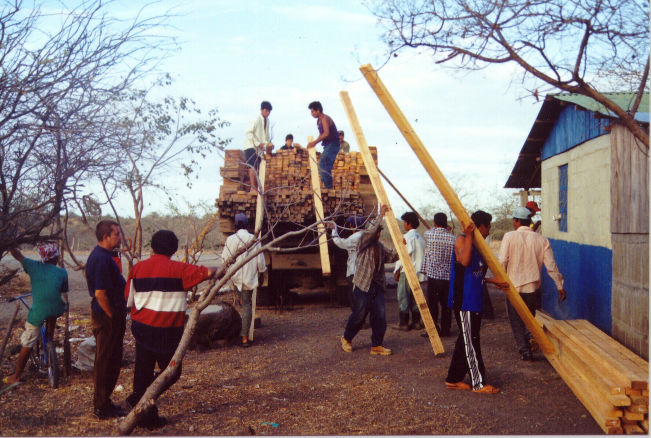 Pacora villagers and workers in the ELCA group unload lumber for new homes.