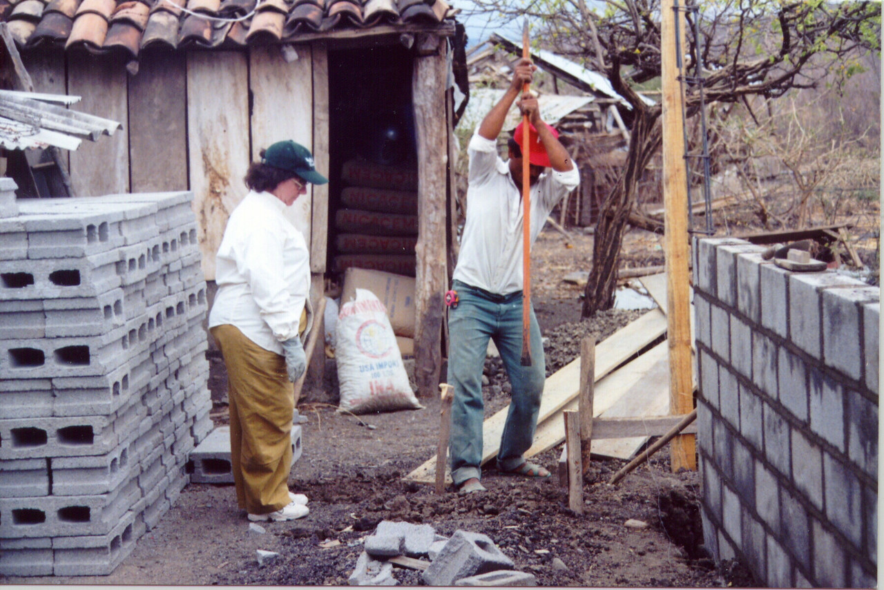 The Rev. Nancy M. Curtis (left), Kane, Pa., assists in digging a footer for a new home in Pacora.