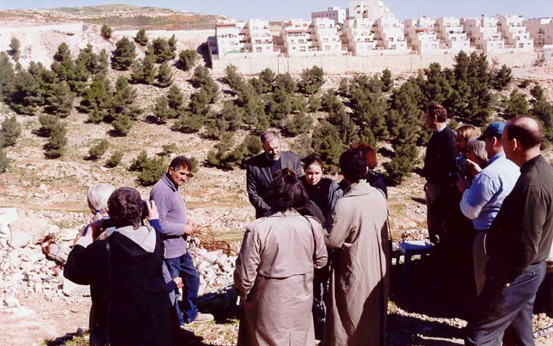 ELCA communicators stand on ruins of homes demolished by Israeli authorities in the Shu'fat Refugee Camp. Demolished homes overlook a new Israeli settlement on Palestinian land.