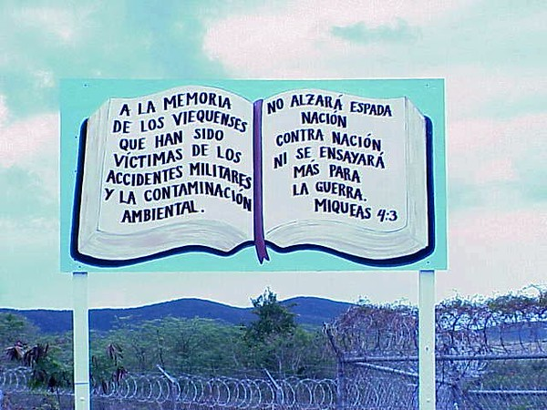"The sign, erected near the entrance of Camp Garcia, Vieques, says, ""In memory of those Viequenses who were victimized by military accidents and a contaminated island.""  The text on the right is a verse from the book of Micah:  ""Nation shall not lift up sword against nation, neither shall they learn war anymore."""