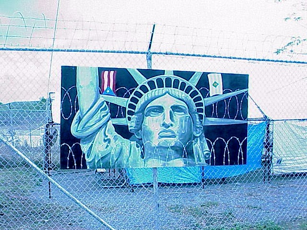 The painting, depicting the Statute of Liberty weeping, hangs on a fence at Camp Garcia.  The fence separates U.S. Navy and civilian land on Vieques.