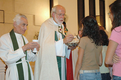 Bishop Mark Hanson, ELCA presiding bishop and Lutheran World Federation (LWF) president, center, serves communion at a worship service Aug. 28 at Good Shepherd Lutheran Church, Amman, Jordan.  Assisting Hanson is, left, Rev. Numan Smir, founder and former pastor of Good Shepherd.