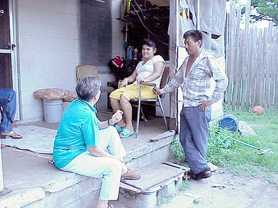 Margarita Romo (left), director for Farmworkers Self-Help, consults with farm workers in Dade City.