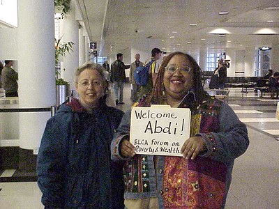 Jean Morehouse (left) and Loretta Horton (right) wait at Chicago O'Hare Airport to greet an international guest.