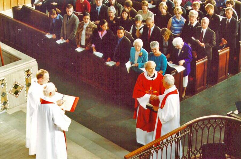The Rev. Lowell G. Almen, right front, congratulates Presiding Bishop-Elect Hanson before the installation. Almen formally presented Hanson for the rite of installation.