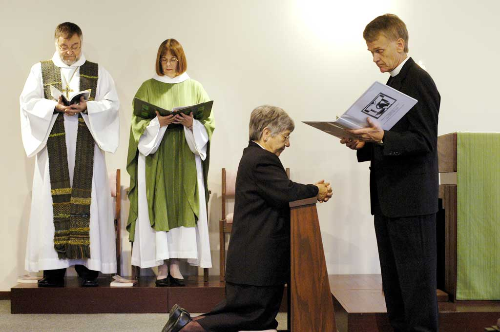 """""""May she do justice, love kindness and walk humbly with you,"""" the Rev. Stanley N. Olson (right), executive director, ELCA Division for Ministry, prays as he installs Sister E. Anne Keffer (kneeling) as directing deaconess, Deaconess Community of the ELCA. The Rev. Raymond L. Schultz, national bishop, Evangelical Lutheran Church in Canada, and the Rev. Rebecca S. Larson, executive director, ELCA Division for Church in Society, stand in the background."""