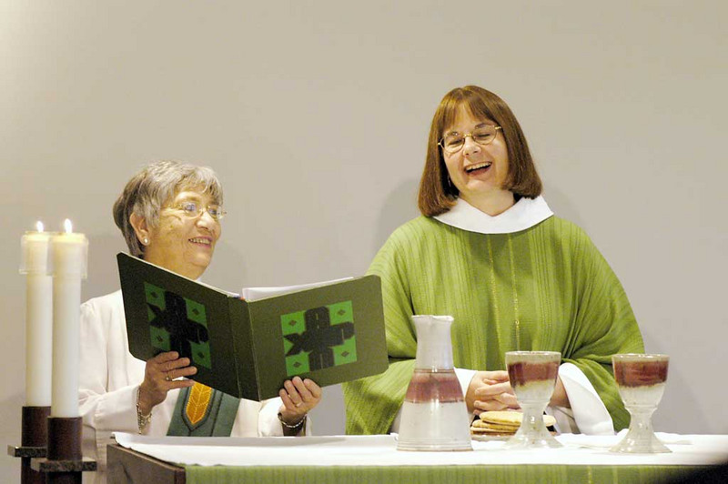 Sister E. Anne Keffer (left), directing deaconess, Deaconess Community of the ELCA, assists as the Rev. Rebecca S. Larson, executive director, ELCA Division for Church in Society, presides at the sacrament of Holy Communion.