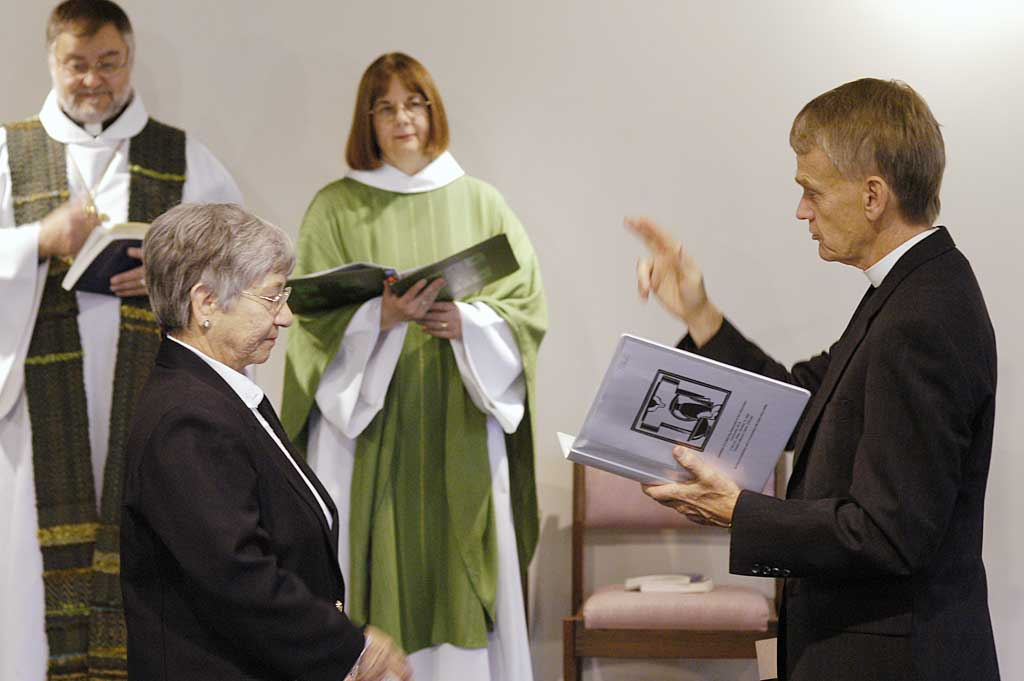 The Rev. Stanley N. Olson (right), executive director, ELCA Division for Ministry, makes the sign of the cross as he installs Sister E. Anne Keffer (foreground left) as directing deaconess, Deaconess Community of the ELCA. The Rev. Raymond L. Schultz, national bishop, Evangelical Lutheran Church in Canada, and the Rev. Rebecca S. Larson, executive director, ELCA Division for Church in Society, stand in the background.
