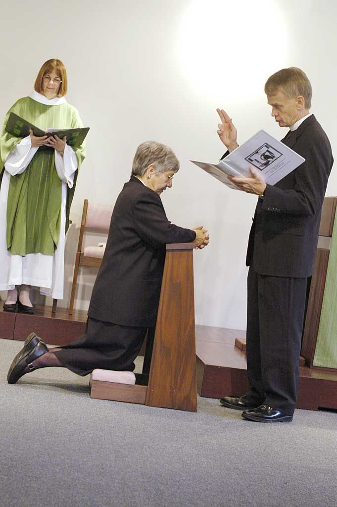 """Almighty God guide, bless and keep you, that you may be faithful in the ministry to which you have been called and consecrated,"" the Rev. Stanley N. Olson (right), executive director, ELCA Division for Ministry, prays as he installs Sister E. Anne Keffer (kneeling) as directing deaconess, Deaconess Community of the ELCA. The Rev. Rebecca S. Larson, executive director, ELCA Division for Church in Society, stands in the background."
