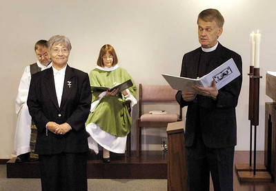 The Rev. Stanley N. Olson (right), executive director, ELCA Division for Ministry, reads from the Service of Installation and Covenanting, presenting Sister E. Anne Keffer (left) as directing deaconess, Deaconess Community of the ELCA. The Rev. Raymond L. Schultz, national bishop, Evangelical Lutheran Church in Canada, and the Rev. Rebecca S. Larson, executive director, ELCA Division for Church in Society, are seated in the background.