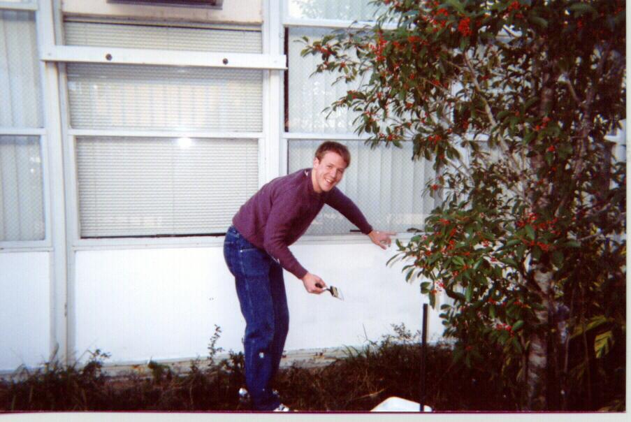 Gathering participant, Chris Haman, North Dakota State University, paints JFK High School exterior window surface.