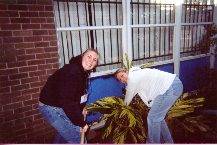 Gathering participants paint exterior window surfaces at JFK High School.