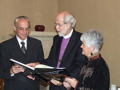 Bishop D. Dr. Christoph Klein, left, of the Evangelical Lutheran Church of the Augsburg Confession, presents LWF President and ELCA Presiding Bishop Mark. S. Hanson a book during Hanson's visit to Sibiu/Hermannstadt, Transylvania, on Nov. 1. At right is Hanson's wife, Ione.
