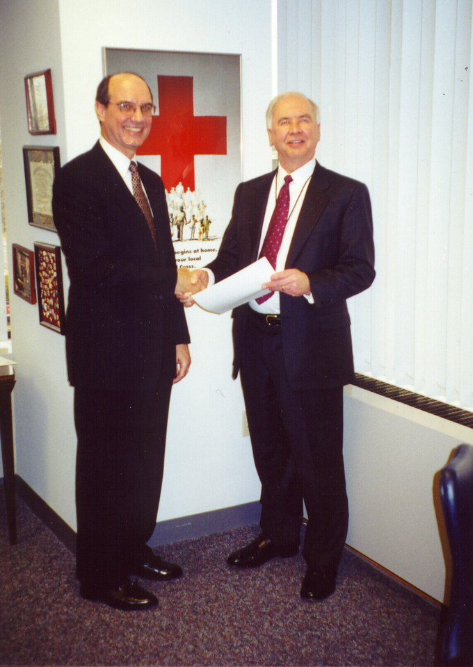 """The Rev. Gilbert B. Furst (right) director for Lutheran Disaster Response, and John A. Clizbe, vice president for disaster services, Red Cross, shake hands after signing the """"Statement of Understanding"""" between the American Red Cross and Lutheran Disaster Response on Jan. 17, in Washington, D.C."""