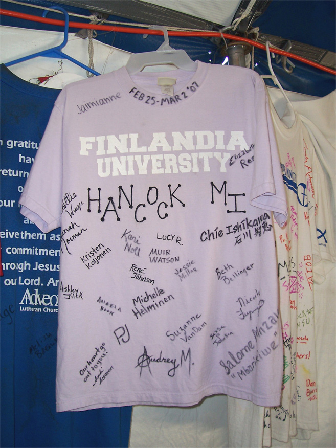 """T-shirts adorn the interior of the """"dining tent"""" at Camp Atonement, Metairie, La. It has become tradition for volunteers to sign and leave behind a t-shirt representing their school and/or home congregation. Finlandia University is one of 28 colleges and universities of the ELCA."""