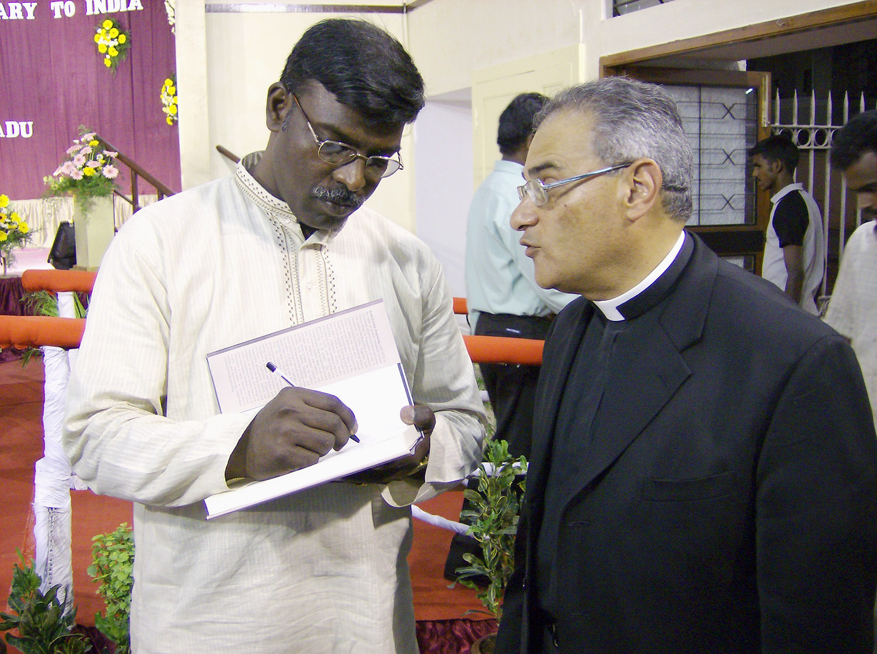"""Dr. Daniel Jeyaraj (left) signs a copy of his book, """"Bartholomaeus Ziegenbalg: The Father of Modern Protestant Mission - An Indian  Assessment,"""" for the Rev. Rafael Malpica-Padilla, executive director,  ELCA Global Mission."""