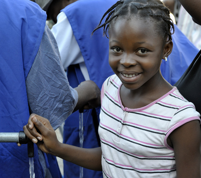 A girl in the Belair neighborhood of Port-au-Prince who survived Haiti's devastating January 12 earthquake enjoys safe water for the first time on January 21 after Norwegian Church Aid, a member of the ACT Alliance, installed a water system that provides homeless families with piped in water points. Photo by Paul Jeffrey/ACT Alliance.