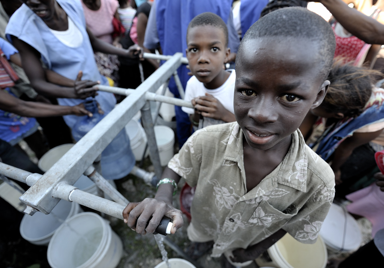Boys in the Belair neighborhood of Port-au-Prince who survived Haiti's devastating January 12 earthquake enjoy safe water for the first time on January 21 after Norwegian Church Aid, a member of the ACT Alliance, installed a water system that provides homeless families with piped in water points. Photo by Paul Jeffrey/ACT Alliance.