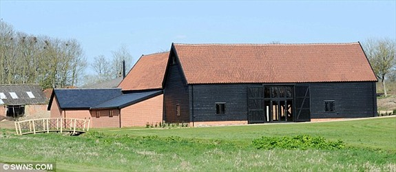 The Medieval Barn after renovation works, seen within the setting of the new grounds that are still to be planted.