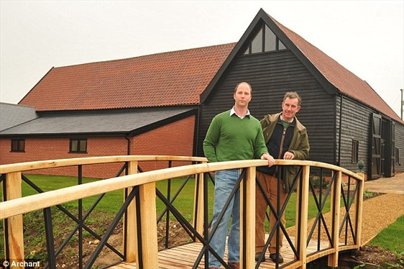 The Medieval Barn after renovation works, seen within the new grounds that are still to be planted and the bridge over the stream with the owner, Mr Robert Rouse, and Barn manager,  Mr Paul Daws.