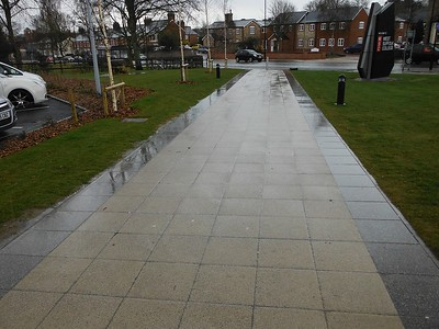 Different coloured paving used to define the space and circulation, but as ever, value engineering has steered the materials to a different specification and colour finish.