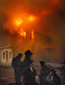 Firefighters prepare to attack flames coming from homes in the 500 block of Howard Street in Frackville Sunday morning.