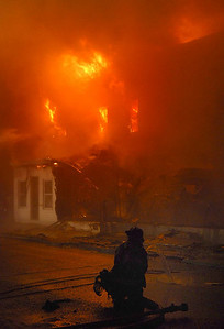 A firefighter waits for water as flames shoot from homes in the 500 block of Howard Street in Frackville early Sunday morning.