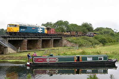 As 'Little Flower' passes by on the River Nene, 56057 awaits entry into Wansford station on 22/07/2005.