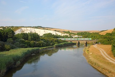 313217 on the 2C52 1811 Brighton to Seaford at Southerham crosses the River Ouse and passes the white chalk cliffs above the Cliffe Industrail estate on the 21st July 2018