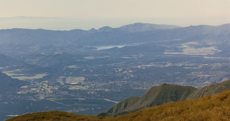 The Ojai Valley and Lake Casitas from Chief Peak, 11/1984. A piece of Santa Cruz Island is visible through the haze over the Pacific Ocean.