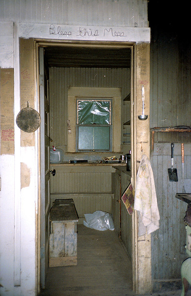 """Bless this Mess"" - looking into the kitchen of Madulce Cabin from the sleeping quarters - a piece of the stove is visible in the far lower right of the frame."