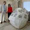 In this photo taken Thursday, Sept. 22, 2011, Joan Weinstein, associate director of the Getty Foundation, right, and the Getty Research Institute, Andrew Perchuk, deputy director, pose in front of an art  piece made of Dolomite rock and transfer letters as part of the upcoming show: Pacific Standard Time at The Getty Center in Los Angeles. (AP Photo/Damian Dovarganes)