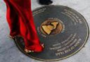 A woman arriving for tonight's Grammy awards looks at a Grammy sidewalk plaque,