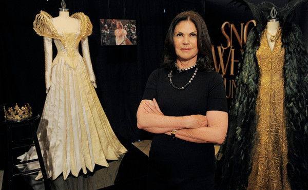 "This May 3, 2012 photo shows Academy Award-winning costume designer Colleen Atwood posing with two costumes from the film ""Snow White and the Huntsman"" in Los Angeles. The costumes, designed by Atwood, were worn by actress Charlize Theron in the film. (AP Photo/Chris Pizzello)"
