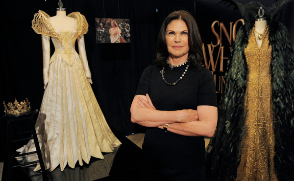 """This May 3, 2012 photo shows Academy Award-winning costume designer Colleen Atwood posing with two costumes from the film """"Snow White and the Huntsman"""" in Los Angeles. The costumes, designed by Atwood, were worn by actress Charlize Theron in the film. (AP Photo/Chris Pizzello)"""