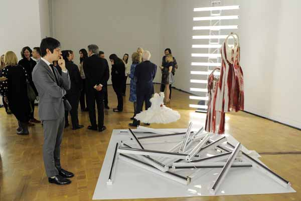 """This Wednesday, Feb. 23, 2011 photo shows a guest at a preview of the art exhibition """"Rodarte: States of Matter,"""" as he studies the installation """"Red Collection,"""" at the Museum of Contemporary Art in West Hollywood, Calif.  (AP Photo/Chris Pizzello)"""