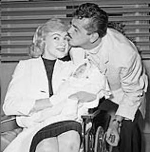 """FILE - In this June 28, 1959 file photo, with cigar in hand, comedian Ernie Kovacs kisses his wife Edie Adams as she holds their daughter Mia at Cedars of Lebanon Hospital in Los Angeles, Calif. A new six-disk boxed set, """"The Ernie Kovacs Collection,"""" curates surviving treasures stretching from 1951 through his untimely death in 1962 will be released April 19, 2011. (AP Photo, file)"""