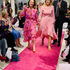 The dynamic duo — co-Chairwomen Susan Anton Pasanen of North Andover and Elaine Zouzas Thibault of Chelmsford — strut their stuff as emcee Chuck Steelmn of  Neiman Marcus, announces them.