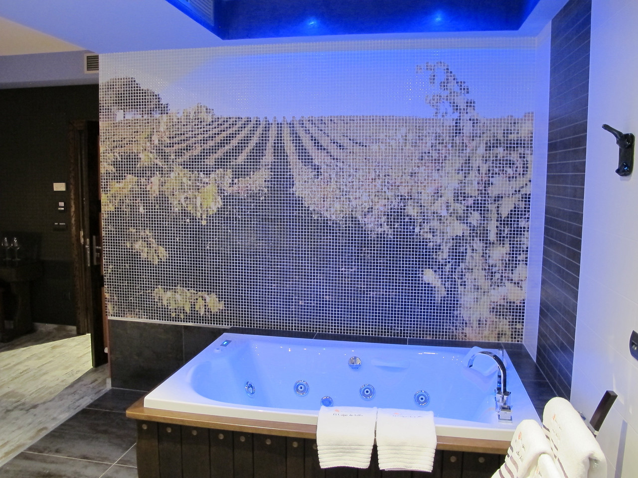 Behind the jacuzzi is a tiled wall with a mosaic of a nearby vineyard.