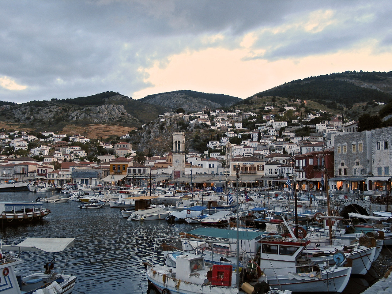 "There is one main town, known simply as ""Hydra port"" (pop. 2,526 in 2001). It consists of a crescent-shaped harbor, around which is centered a strand of restaurants, shops, markets, and galleries that cater to tourists and locals (Hydriots). Steep stone streets lead up and outwards from the harbor area. Most of the local residences, as well as the hostelries on the island are located on these streets."