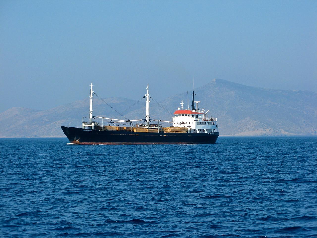 We pass a freighter hauling lumber between islands.