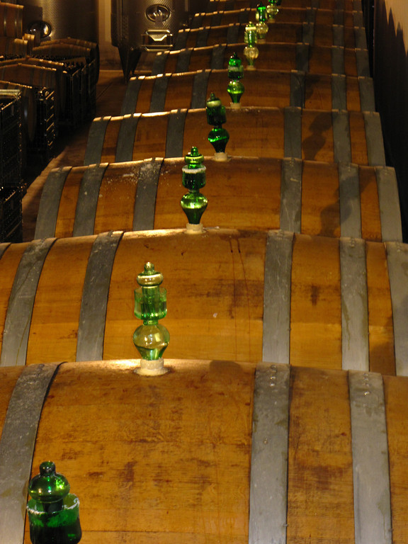 The green glass items in the top of each barrel alert the winemaker when it is time to top off the barrel as evaporation occurs.