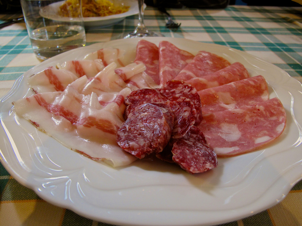 An appetizer plate of salamis and uncured bacon.