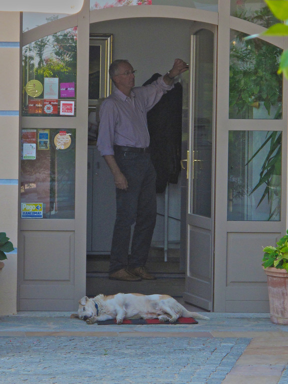Angelo Rocca, the winery owner watches as his dog guards the front door.