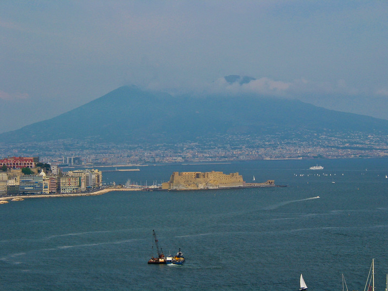 Mount Vesuvius is a stratovolcano in the Gulf of Naples, Italy, about 9 kilometres (5.6 mi) east of Naples and a short distance from the shore. It is one of several volcanoes which form the Campanian volcanic arc. Vesuvius consists of a large cone partially encircled by the steep rim of a summit caldera caused by the collapse of an earlier and originally much higher structure.<br /> Mount Vesuvius is best known for its eruption in AD 79 that led to the burying and destruction of the Roman cities of Pompeii and Herculaneum.